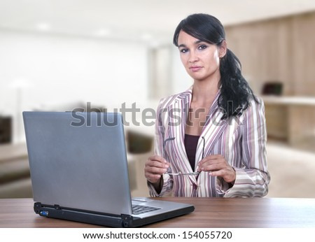 Pretty young office worker sitting at desk  - stock photo