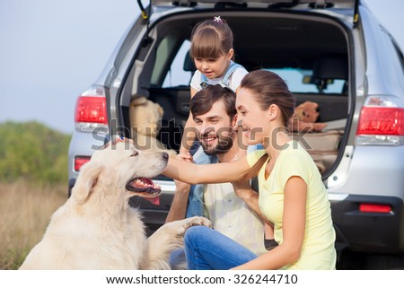 Pretty young parents and their daughter are sitting near car in the nature. They are playing with dog and smiling. The father is holding girl on shoulders. The woman is stroking pet