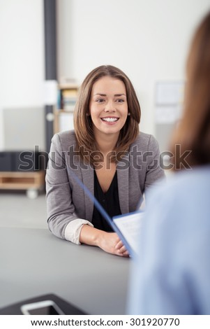Pretty Young Professional Job Seeker Woman Being Interviewed by a Manager Inside the Office with a Happy Facial Expression. - stock photo