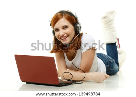 Pretty young red-haired woman in headset with a laptop lies on a white background. - stock photo