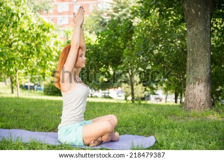 Pretty young red-haired woman wearing white T-shirt and mental shorts doing yoga sitting aside on the blue mat in the park