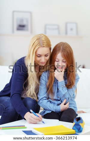 Pretty young redhead girl doing homework with her mother as they sit together on a sofa working on paperwork - stock photo