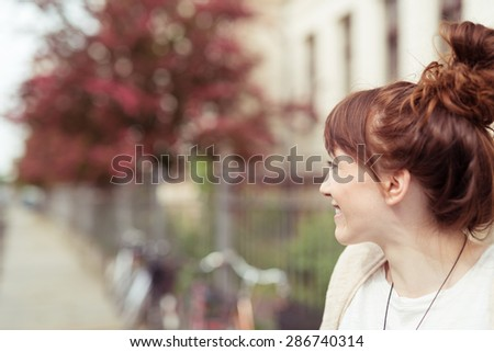 Pretty young redhead woman standing smiling as she waits on an urban street looking down the road away from the camera, with copyspace - stock photo