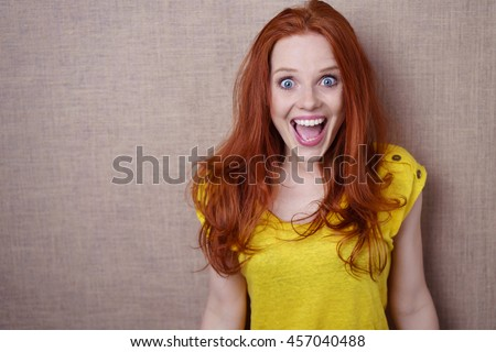 Pretty young redhead woman with a happy surprised expression of wide eyed delight standing against a beige background with copy space - stock photo