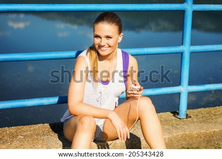 Pretty young runner woman with smart phone and headphones sitting by the lake on the bridge. Teenage fit blonde Caucasian girl in sportswear making a running playlist. - stock photo