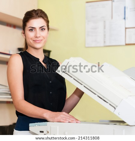 Pretty young secretary using a copy machine - stock photo