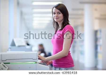 pretty young secretary using a copy machine (shallow DOF; color toned image) - stock photo