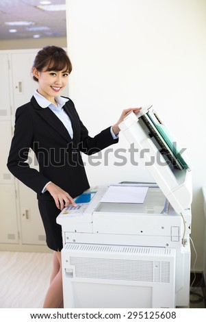 pretty young secretary using  photocopy machine in office - stock photo
