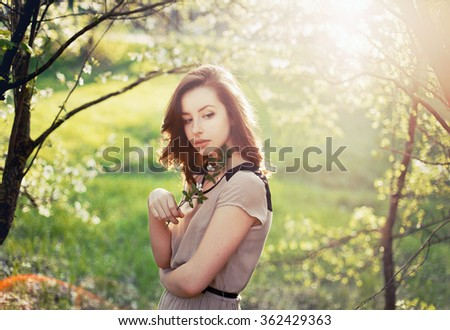 Pretty young sensual brunette woman posing in spring in garden trees in blossom evening sunlight with flares