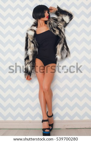 Pretty young sexy fashion woman with short black hair posing on studio dressed in bodysuit and coat