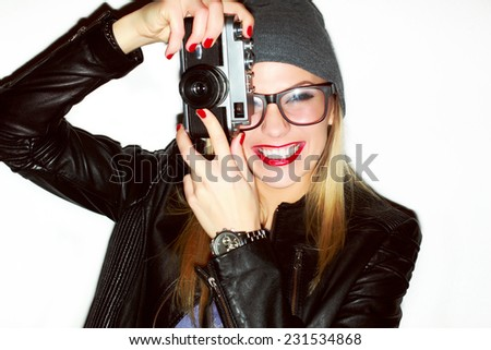 Pretty young sexy smiling happy fashion photographer woman with camera making photo-shooting with old film camera dressed trendy hipster outfit and colorful makeup red lips  - stock photo