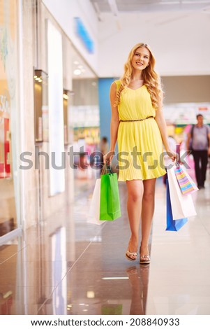 Pretty young shopper with paperbags walking down mall