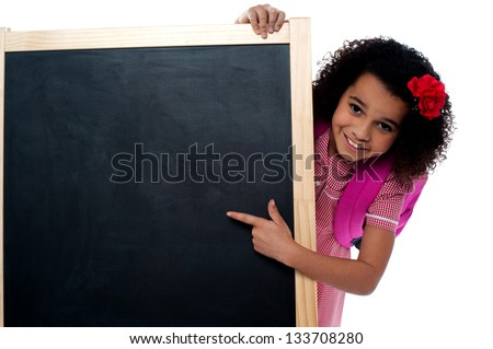 Pretty young smart student pointing towards blank standing board. - stock photo