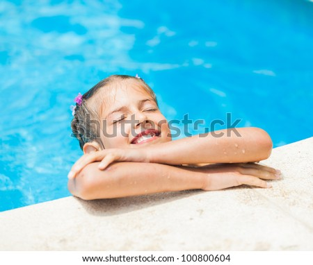 Pretty young smiling girl near a side of the pool - stock photo