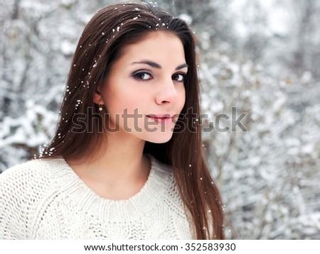 Pretty young smiling happy woman posing outdoor in winter sensual closeup portrait