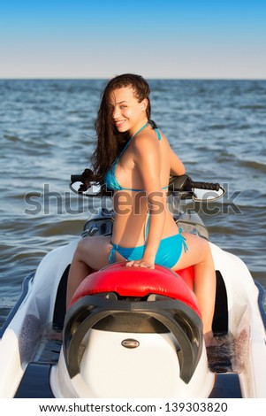 Pretty young smiling lady posing on the wave runner  - stock photo