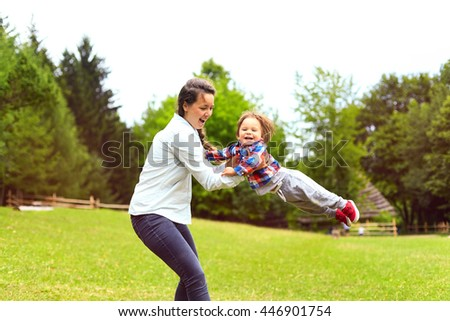 Pretty young smiling mother throwing up cheerful child in the park. Woman and toddler son having fun together in summer sunny day. Happy healthy family, love concept,positive human emotions, feelings. - stock photo