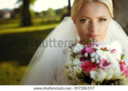 Pretty young smiling stylish blonde bride under the veil