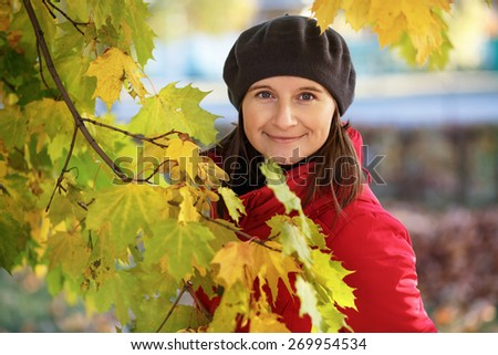 Pretty young smiling woman in a beret and red jacket and surrounded by colorful autumn foliage. Shallow depth of field. Focus on the model's face. - stock photo