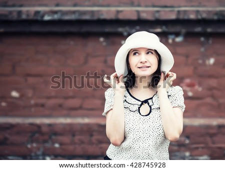 Pretty young smiling woman in a white blouse and hat posing on old vintage brick wall background. Girl holds the edges of the hat by hand. Toned photo with copy space. Vintage style photo. - stock photo