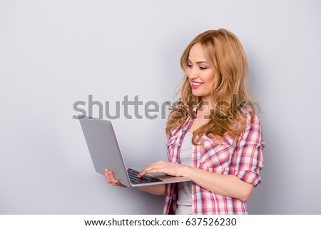 Pretty young smiling woman in casual clothes chatting in social network using laptop