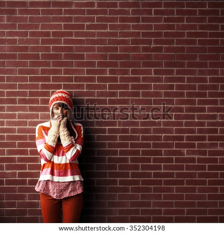 Pretty young student girl getting cold posing near big red bricks wall in red style sweater and hat  - stock photo