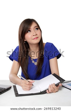 Pretty young student looking up thinking while writing on notebook, isolated on white background - stock photo