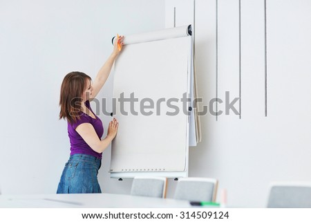 Pretty young student or business woman writing on a paper board during a class or business meeting - stock photo