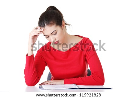 Pretty young student woman in casual clothes sitting at the desk and thinking, isolated on white