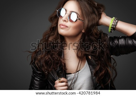 Pretty young stylish girl with long curly hair posing on black background with one hand up, dressed in rock style outfit, black leather jacket and round sunglasses. Youth style, fashion. Portrait. - stock photo