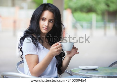 pretty young teen drinking coffee outside a cafe