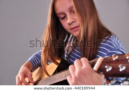 Pretty young teen girl playing acoustic guitar - stock photo