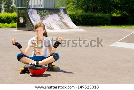 Pretty young teenage girl in rollerblades sitting meditating on the tarmac at a skate park sitting n the lotus position with her eyes closed - stock photo