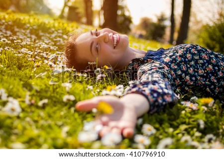 Pretty young teenage girl relaxing on a grass - stock photo