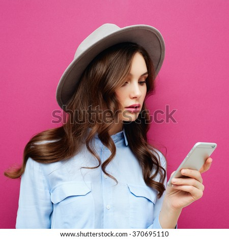 Pretty young teenage girl typing and reading text message on her new modern cell phone mobile  on a pink background - stock photo