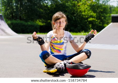 Pretty young teenager sitting meditating in her sporting gear as she sits cross-legged on the asphalt at the skate park with a look of blissful serenity - stock photo