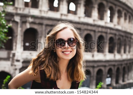 Pretty young tourist traveling in Rome, Italy (with Colosseum on the background) - stock photo