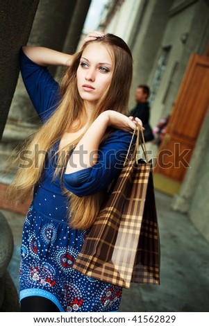 pretty young upset woman with shopping bags outdoor - stock photo