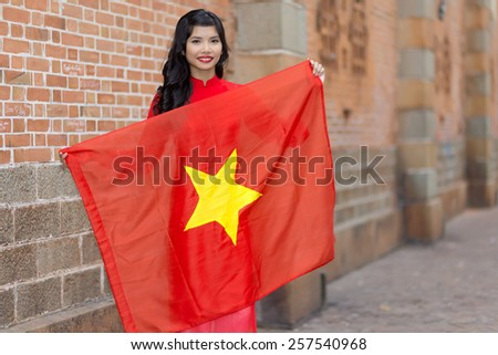 Pretty young Vietnamese woman with a lovely friendly smile holding up a the national flag of Vietnam as she stands in an urban street against a brick wall - stock photo