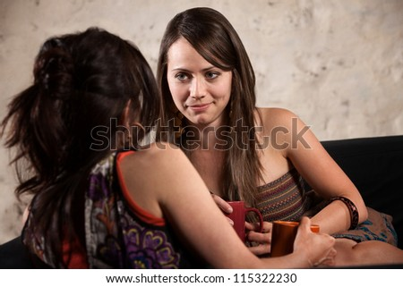 Pretty young white woman listening to friend talk on sofa - stock photo