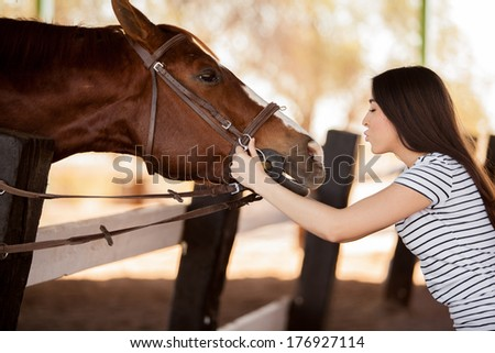 Pretty young woman about to kiss a horse in a ranch