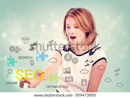 Pretty young woman activating an SEO interface on a virtual screen with scattered SEO icons for optimizing a website - stock photo