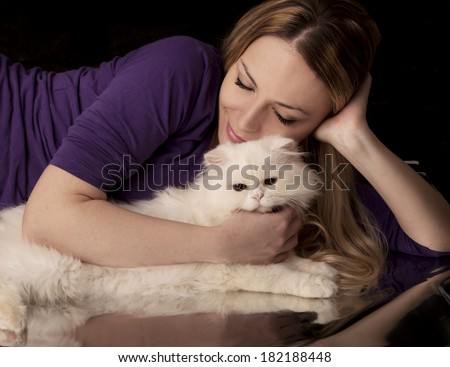 Pretty young woman and a white cat - stock photo