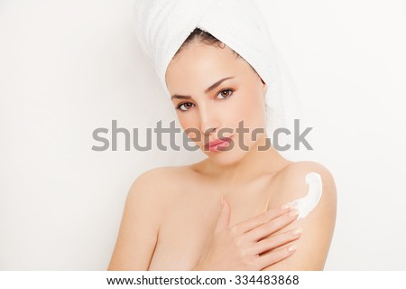 pretty young woman applying cream on her body, studio white