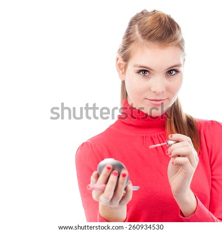 pretty young woman applying lip gloss (on white background) - stock photo