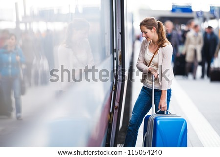 Pretty young woman at a train station - stock photo