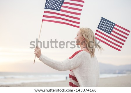 Pretty Young Woman at the Beach holding American Flags facing the ocean - stock photo