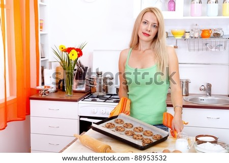 Pretty young woman baking cookies in the kitchen