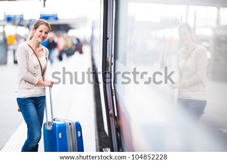 Pretty young woman boarding a train (color toned image) - stock photo
