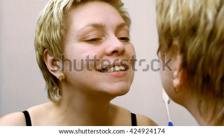 Pretty young woman brushing teeth in front of mirror. Everyday dental cleaning hygiene scene. - stock photo